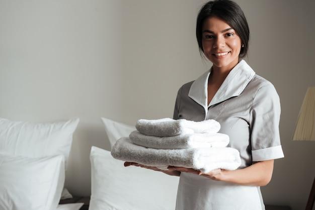 Portret hotelowa gosposia trzyma świeże czyste złożone ręczniki