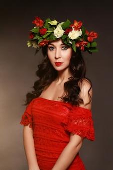 Portret idealnej kobiety z wieńcem kwiatów na głowie i czerwoną sukienką.
