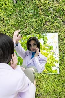 Portret illusion stylowa dziewczyna w okularach przeciwsłonecznych i sukienka siedzieć na plaży trzymając lustra z odbiciem piasku i kamieni. nowa wizja koncepcji projektów modowych. cyfrowy narcyzm