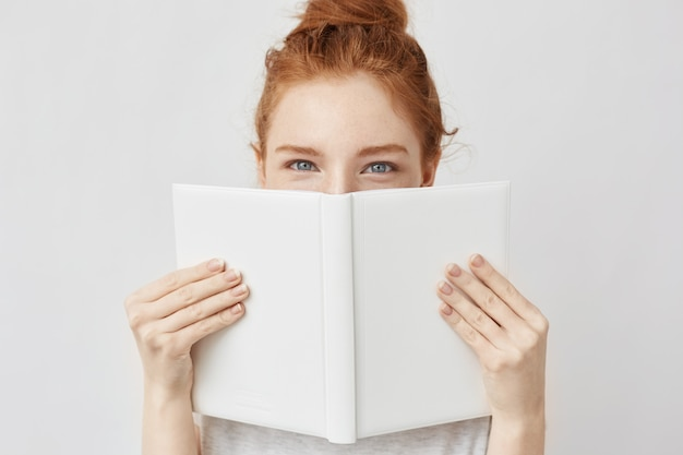 Portret imbirowa kobieta chuje za książką.