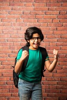 Portret indyjskiego azjatyckiego małego chłopca w stroju casual z tornisterem lub plecakiem, stojący przy ścianie z czerwonej cegły