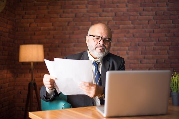 Portret indyjskiego azjatyckiego starszego biznesmena rzucającego lub czytającego dokumenty siedząc przy biurku z laptopem