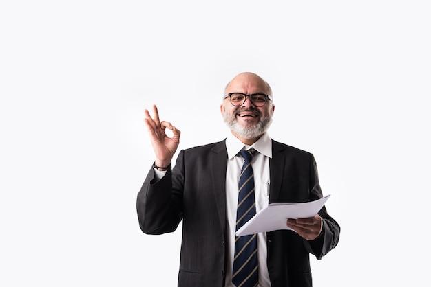 Portret indyjskiego azjatyckiego starszego biznesmena trzymającego lub czytającego papierowe dokumenty, stojąc na białym tle