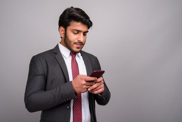 Portret indyjskiego biznesmena przy użyciu telefonu komórkowego na szarym tle