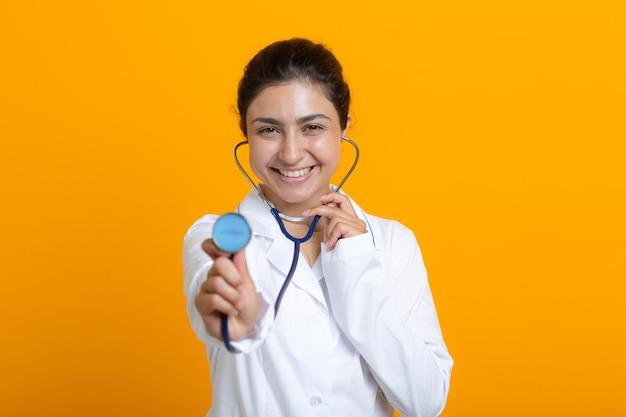 Portret indyjskiej lekarki w białej sukni medycznej odizolowanej na żółtym tle