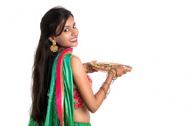 Portret indyjskiej tradycyjnej dziewczyny trzymającej diya, dziewczynę z okazji diwali lub deepavali z trzymającą lampę naftową podczas festiwalu światła na białej powierzchni