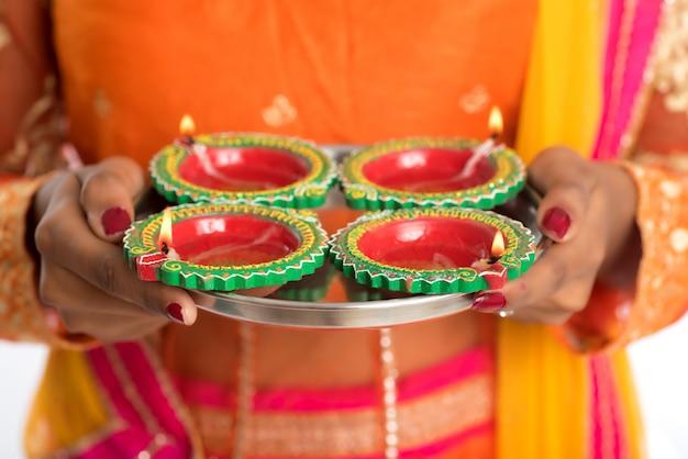 Portret indyjskiej tradycyjnej dziewczyny trzymającej diya, dziewczynę z okazji diwali lub deepavali z trzymającą lampę naftową podczas festiwalu światła na białej ścianie