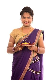 Portret indyjskiej tradycyjnej dziewczyny trzymającej pooja thali z diya podczas festiwalu światła na białej przestrzeni. diwali lub deepavali