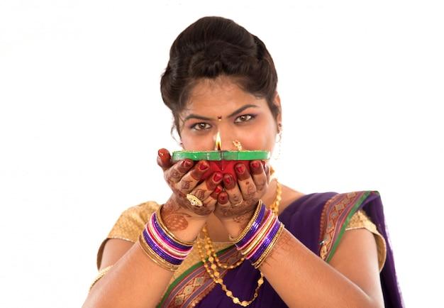 Portret indyjskiej tradycyjnej dziewczyny trzymającej zdjęcie diya, diwali lub deepavali z kobiecymi rękami trzymającymi lampę naftową podczas festiwalu światła na białej przestrzeni