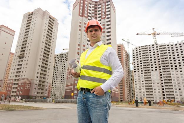 Portret inspektora budowlanego stojącego na placu budowy