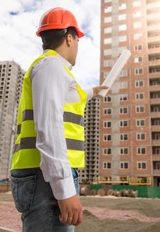 Portret inspektora budowlanego wskazującego na budynek w budowie