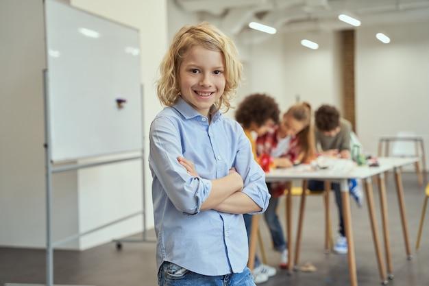 Portret inteligentnego faceta radosnego chłopca uśmiechającego się do kamery stojącej z rękami skrzyżowanymi podczas pozowanie do