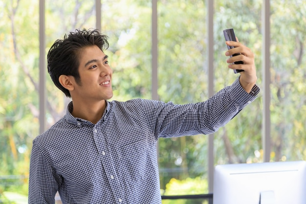 Portret inteligentnego młodego biznesmena azjatyckiego za pomocą inteligentnego telefonu komórkowego, aby zrobić zdjęcie selfie w pokoju biurowym.