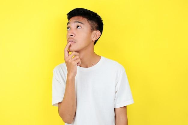 Portret inteligentnego młodego człowieka azjatyckiego myślenia i patrzeć w górę. inteligentny młody azjata ubrany w białą koszulkę, myślący i patrzący w górę, na żółtym tle