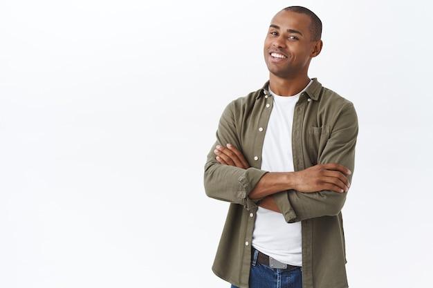 Portret inteligentnego, profesjonalnego afroamerykanina, stojącego z rękami skrzyżowanymi na klatce piersiowej, pewna pozy