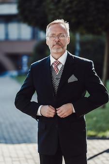 Portret inteligentnego zamożnego i przemyślanego atrakcyjnego dojrzałego biznesmena z siwymi włosami.