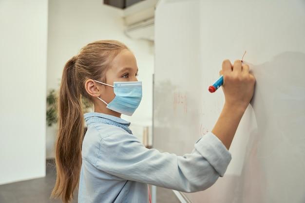 Portret inteligentnej małej uczennicy noszącej maskę ochronną podczas pisania pandemii koronawirusa