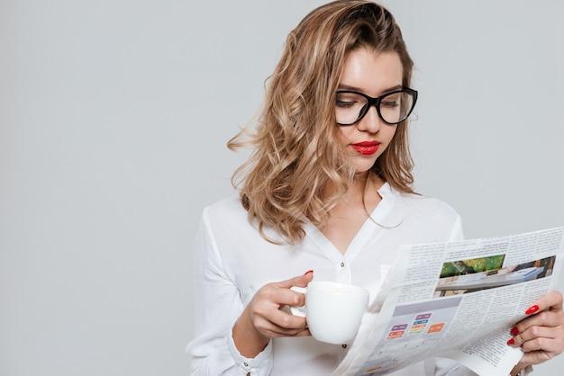Portret inteligentnej młodej kobiety w okularach, czytającej gazetę i pijącej filiżankę kawy na białym tle na białej ścianie