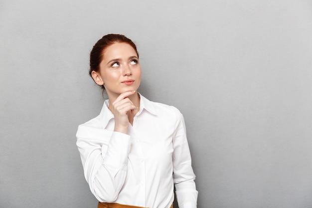 Portret inteligentnej rudej bizneswoman 20s w formalnym stroju dotyka jej podbródka i pozuje w biurze na białym tle nad szarym