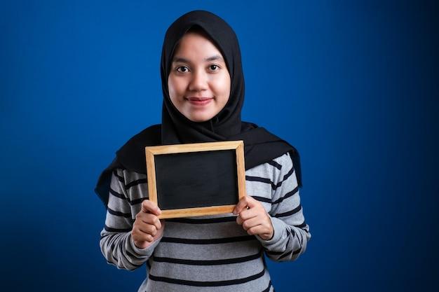Portret inteligentnej szczęśliwej udanej azjatyckiej kobiety muzułmańskiej noszącej hidżab uśmiechający się do kamery, trzymając i pokazując pustą tablicę lub tablicę kredową z miejscem na kopię