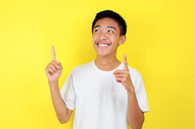 Portret inteligentny i szczęśliwy młody człowiek azjatyckich myślenia i patrzeć w górę. szczęśliwy młody azjata ubrany w białą koszulkę, myślący i patrzący w górę, na żółtym tle