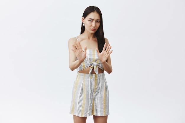 Portret intensywnie niezadowolonej i zmartwionej uroczej azjatyckiej kobiety w dopasowanych ubraniach, trzymającej dłonie przy klatce piersiowej w geście nie lub zatrzymania, odmawiającej spróbowania alkoholu