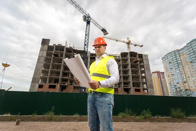 Portret inżyniera budowlanego w kasku na placu budowy z działającymi dźwigami