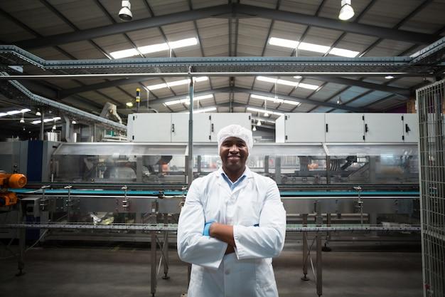 Portret inżyniera fabrycznego pozycja z jego rękami krzyżować