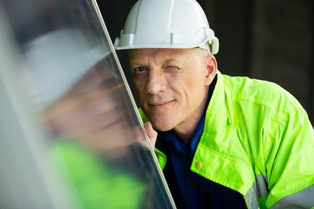 Portret inżyniera patrząc na panel z ogniwami słonecznymi