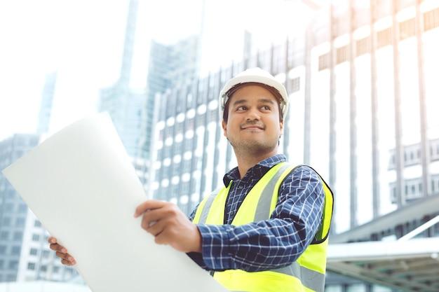 Portret inżyniera pracownik budowlany azjatycki mężczyzna trzyma papier w rolce rysunku plan strukturalny bezpieczeństwa