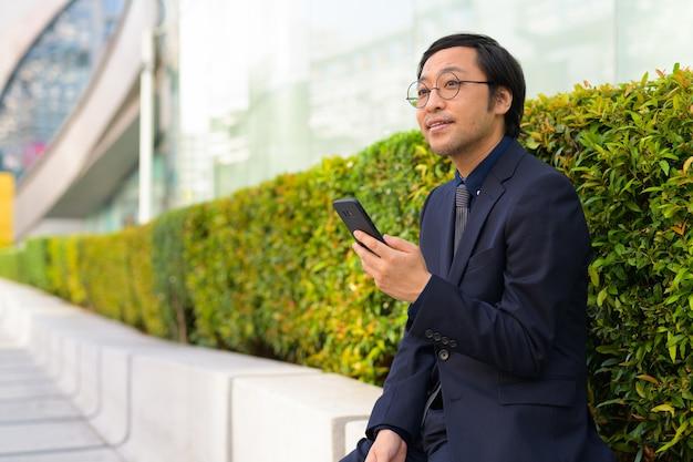 Portret japońskiego biznesmena uzyskiwanie świeżego powietrza z naturą w mieście na zewnątrz