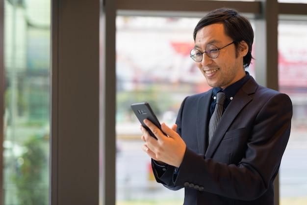 Portret japońskiego biznesmena w biurze przy oknie