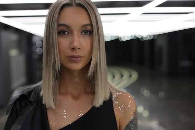 Portret jasnej dziewczyny o niebieskich oczach i srebrnych cekinach na szyi i ramieniu, która stoi w pomieszczeniu z jasnym światłem na suficie i patrzy bezpośrednio w kamerę wysokiej jakości zdjęcie