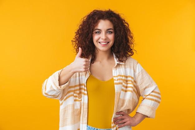 Portret jasnej kobiety w wieku 20 lat z kręconymi włosami, uśmiechniętej i pokazującej kciuki do góry, odizolowanej na żółto