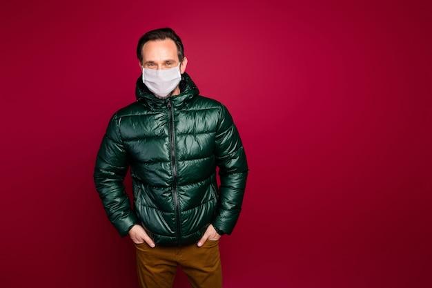 Portret jego dojrzałego faceta w ciepłym płaszczu zimowym masce ochronnej mers cov choroba choroba zapobieganie chorobie dystans społeczny odizolowany na jasnym żywym połysku żywy czerwony kolor tła