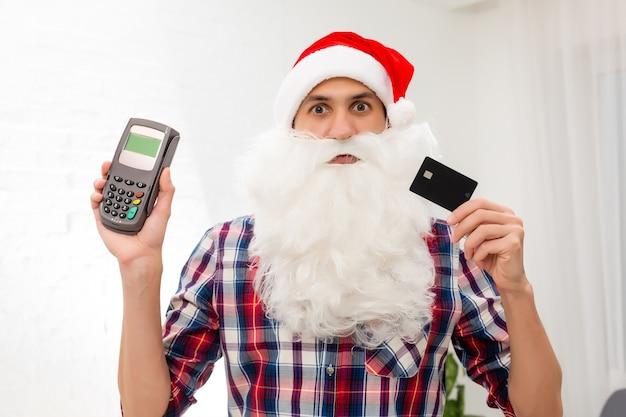 Portret jego ładnego atrakcyjnego mikołaja trzymającego w ręku kartę bankową cyfrowy system terminalowy handel handel