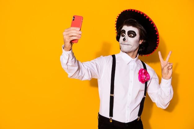 Portret jego ładnego przystojny malowane straszne facet caballero biorąc selfie calavera karnawał uroczystości pokazano v-znak na białym tle jasny żywy połysk żywy żółty kolor tła