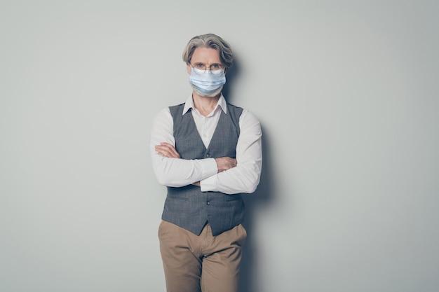 Portret jego ładnego zdrowego siwego mężczyzny w masce ochronnej z gazy stop choroba choroba choroba mers cov nowość grypa zapobieganie pandemii założonymi rękami na białym tle szary kolor tła