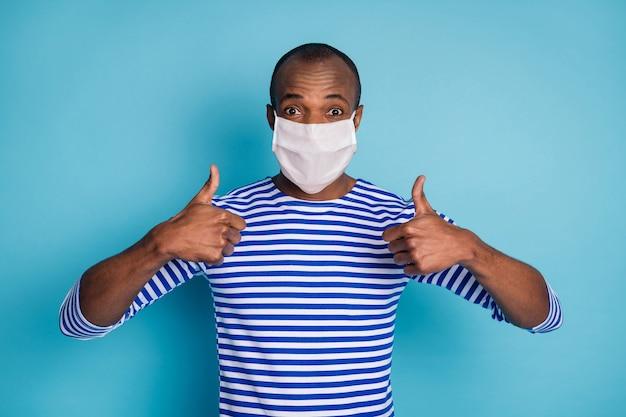 Portret jego ładnej treści zdrowy facet ubrany w maskę bezpieczeństwa pokazujący podwójny kciuk do góry stop mers cov grypa grypa grypa grypa środki zapobiegawcze na białym tle nad niebieskim kolorem tła
