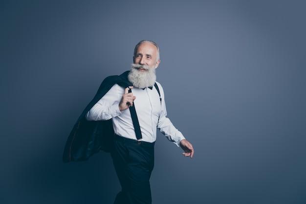 Portret jego miłego atrakcyjnego fajnego, bogatego, bogatego, wesołego, wesołego siwego mężczyzny idącego do pracy rozmowa kwalifikacyjna rekrutacja na białym tle na ciemnoszarym pastelowym tle