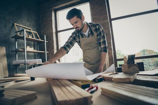 Portret jego miłego, atrakcyjnego, poważnego, ciężko pracującego, doświadczonego mechanika, czytającego plan nowego projektu budowy domu w nowoczesnym wnętrzu w stylu industrialnego loftu