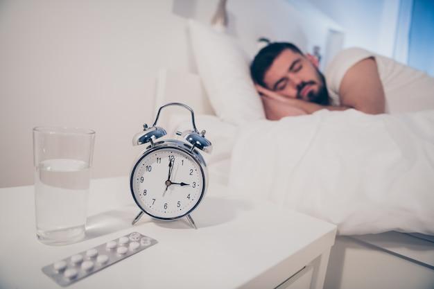 Portret jego miłego atrakcyjnego, sennego spokojnego faceta leżącego na łóżku śpiącego terapia lecznicza leczenie recept w nocy późnym wieczorem dom hotel biały pokój mieszkanie dom