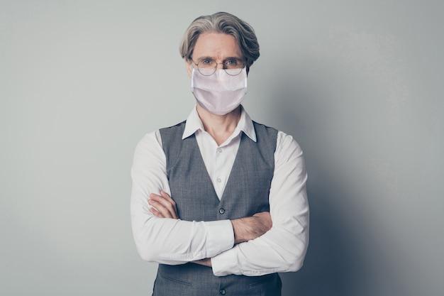 Portret jego miłego inteligentnego starszego siwego mężczyzny emerytowanego emeryta noszącego maskę bezpieczeństwa stop mers cov pandemia grypy pobyt w domu opieka zdrowotna założonymi rękami odizolowany szary kolor tła
