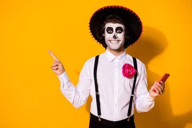 Portret jego miły przystojny straszny wesoły wesoły zadowolony facet za pomocą aplikacji urządzenia 5g demonstruje kopia przestrzeń ogłoszenie calavera uroczystości na białym tle jasny żywy połysk żywy żółty kolor tła