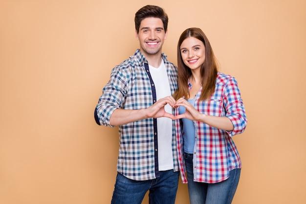 Portret jego on jej ona miła atrakcyjna urocza czuła wesoła para w kraciastej koszuli obejmując pokazujący miesiąc miodowy postać serca na białym tle na beżowym pastelowym kolorze