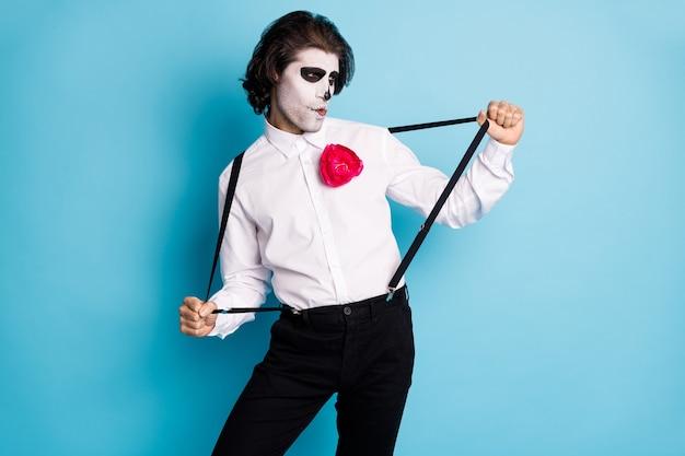 Portret jego przystojny fajny przerażający diaboliczny elegancki dżentelmen facet bawi się ciągnąc szelki taniec motyw okazja na białym tle jasny żywy połysk żywy niebieski kolor tła