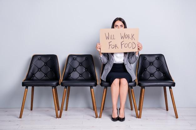 Portret jej atrakcyjna, elegancka, zwolniona pani kierownik siedzi na krześle, trzymając plakat, mówiąc, że będzie pracować dla słów żywnościowych firma redukcja kosztów oferta antykryzysowa na białym tle pastelowy szary kolor tła
