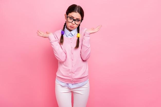 Portret jej jest atrakcyjna, śliczna, ładna, skromna, niepewna, brązowowłosa dziewczyna ubrana w zwykły mundur, nie znajdująca żadnego rozwiązania, na białym tle nad różowym pastelowym kolorem tła