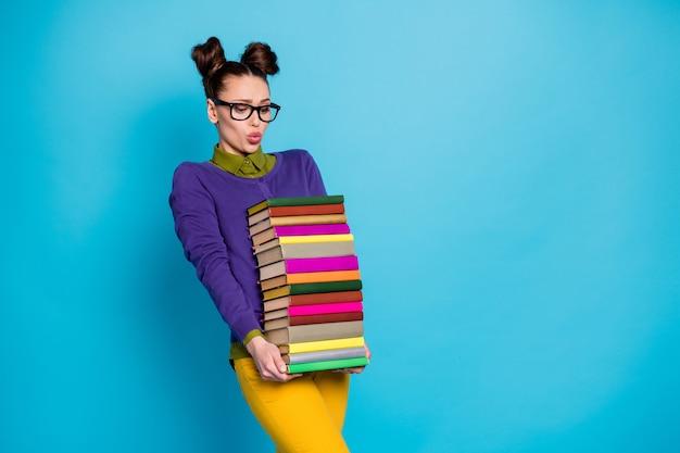 Portret jej jest ładna atrakcyjna całkiem inteligentna mądra zmęczona dziewczyna geek niosąca duże duże ciężkie stosy książek na białym tle na jasny żywy połysk żywy niebieski zielony turkusowy turkusowy kolor tła