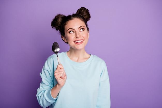 Portret jej jest ładna atrakcyjna całkiem rozmarzona ciekawa wesoła dziewczyna trzyma w ręku łyżkę fantazjuje liczenie kalorii na białym tle fioletowy fioletowy liliowy jasny żywy połysk żywy kolor tła